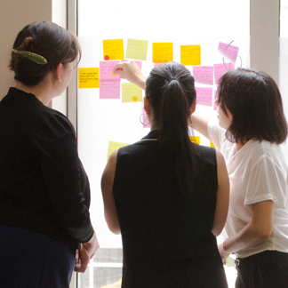 Three people analyzing sticky notes on the wall at a workshop