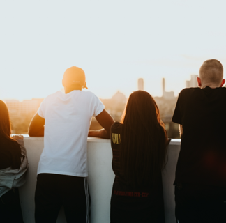 Four young adults standing and facing away from the camera, overlooking the skyline