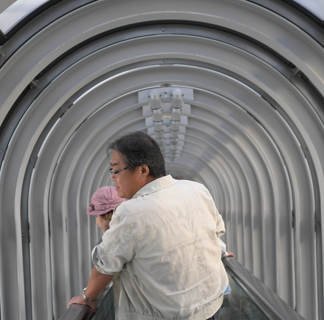 Man standing in an arched hallway holding a baby in front of him, facing away from the camera